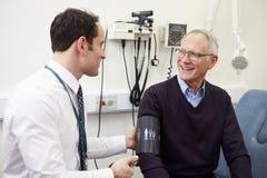 Tension artérielle de docteur Taking Senior Patient dans l'hôpital Photographie stock libre de droits