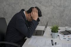 Tension, bad mood, stressed businessman touching his head with h. Ands while using laptop in office Royalty Free Stock Photography