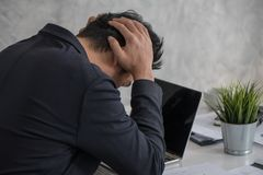 Tension, bad mood, stressed businessman touching his head with h. Ands while using laptop in office Stock Photography