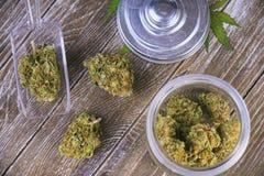 Tension de maître de scout de bourgeons de cannabis sur le pot en verre au-dessus du backg en bois Photos stock