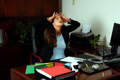 Tension Headache. Female Executive at her desk stretches and massages her head to relieve a tension headache Royalty Free Stock Photo