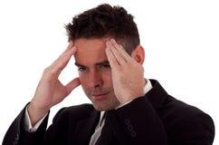 Tensionan o tiene a un hombre de negocios joven un dolor de cabeza Fotografía de archivo libre de regalías