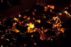 In tensione-carboni d'accensione caldi che bruciano in un barbecue Fotografie Stock Libere da Diritti