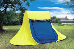 Tent. A blue and yellow tent in a middle of a field stock image