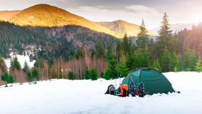 Tent. backpacks. trekking poles, snowshoes on snow mounta Stock Image