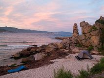 Tent by the beach. Hiking camping with tent on the ocean beach against purple sunset Royalty Free Stock Photo