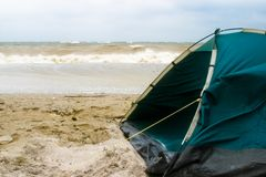 Tent on beach in bad weather. A closeup of a camping tent set up close to the water's edge on a beach. The sand is damp from bad weather and strong winds are Royalty Free Stock Images