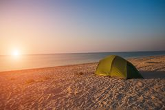 Tent on the beach. Green tent on the beach. Sunset on the sea coast. Camping on the shore of the ocean Stock Photography