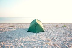 Tent on the beach. Green tent on the beach. Sunset on the sea coast. Camping on the shore of the ocean Royalty Free Stock Photos