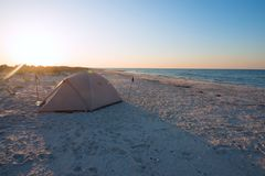Tent on the beach in a rays of rising sun. Magic camp on the shore of the wild sea. Back light Stock Photography