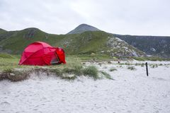 Tent on the beach. Red tent on green grass near the sand at Haukland Beach, Lofoten Islands, Norway Royalty Free Stock Image