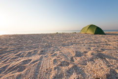 Tent on the beach. Tent on the sea coast. Camping on a sandy beach. Rest in a deserted place Stock Photo