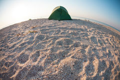 Tent on the beach. Tent on the sea coast. Camping on a sandy beach. Rest in a deserted place Royalty Free Stock Photos