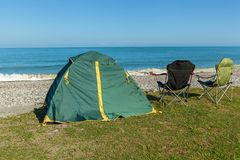 Tent on the beach. With two chairs standing on the grass. ..journey to Georgia Stock Photo