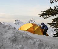 Tent And Boy. A boy greets the morning sunrise high up on Mt. Rainier after camping overnight royalty free stock images