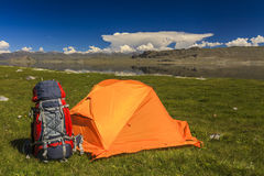 Tent camp and backpack on the side of the stream Royalty Free Stock Photos