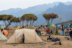 Tent camp on mountain. Kilimanjaro, with its three volcanic cones, Kibo, Mawenzi, and Shira, is a dormant volcano in Kilimanjaro National Park, Tanzania and the Royalty Free Stock Photo