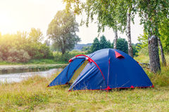 Tent in the camp near the river on the background of trees. Stock Photos