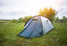 Tent camp standing in forest. Green grassat  sunny morning lights Stock Photo
