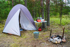 Tent and camp stove in a forest. Royalty Free Stock Photography