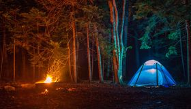 Tent at night lit up with fire pit burning on a campground. Tent in campground lit at Royalty Free Stock Image