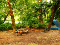 Tent camping. A camp site with wooden table in the forest. Lots of green trees and the river in the background. Taken  in  morning light Stock Image