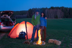 Tent camping car couple stand by bonfire Stock Photos