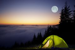 Tent Camping in a Forest. During Full Moon Night. Foggy Mountains Camping royalty free stock photos