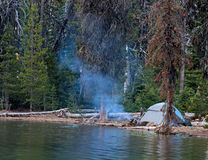 Tent Camping By The Lake In The Mountains. A tent set up for camping by a beautiful lake in the mountains with a lazy stream of smoke Royalty Free Stock Photography