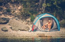 Tent Camping at the Lake. Tent Camping on the Rocky Lake Shore. Outdoor Men Lifestyle stock photo