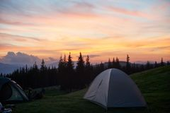 Tent on a camping site in the mountains. Shot of a camping site with tents during beautiful sunset with fiery colorful sky on the background nature peace travel Royalty Free Stock Photo