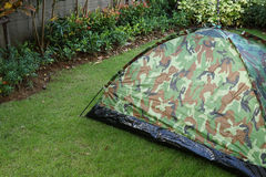 Tent camping wild camouflage style. Design of backyard in green grass garden field Royalty Free Stock Images