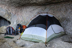 Tent in the cave. Camp, backpacks and one tent in the cave Royalty Free Stock Photo