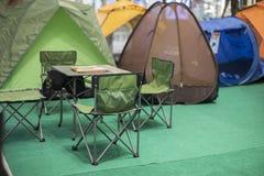 Tent die met bureau en stoelen in pijnboombos kamperen Stock Afbeelding
