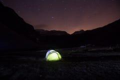 Tent die zich op een bergweiland onder sterrige hemel bevinden Stock Afbeeldingen