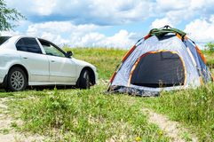 Tent and a dirty white car on blue sky background. The concept of tourism, travel, outdoor recreation