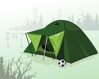 Tent in a forest glade. Camping. Active recreation in nature. House for tourists. Halt hunter. Life in the wild. Suspended on sticks bowler. Soccer ball Royalty Free Stock Photos
