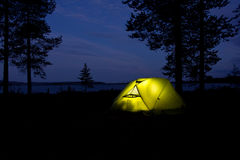 Tent glowing in the darkness in the forest with lake Stock Photos