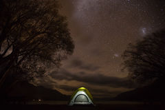 A tent glowing under in a night full of stars Stock Photography