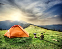 Tent on the hill beneath the mountains Stock Photos