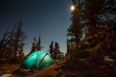 Tent illuminated with light in night forest Royalty Free Stock Photo