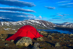 Tent at a Lake in Scandinavia. Red tent at a lake with mountains in the back along the Nordkalottleden in the north of Scandinavia Royalty Free Stock Photos