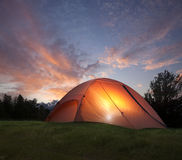 Tent with light inside at dusk near the Grand Teton mountains. An orange tent with a light glowing inside at dusk near the Grand Teton mountains Stock Photography