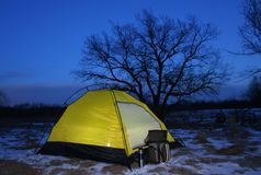 A tent lit up at dusk. Lit tent in winter dusk with the big oak on background royalty free stock photo