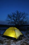 A tent lit up at dusk. Lit tent in winter night with the oak on background royalty free stock photos