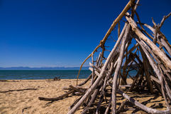 Tent made of wood on a beach. Abel Tasman NP, NEW ZEALAND in February 2016: A tent made out of boughs stands on an empty beach. The sky is blue and the sun is Stock Photo