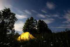 Tent in the middle of the night and clouds. An yellow tent in mountains, in the middle of the night and the wind moving the trees and clouds Stock Image