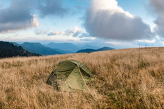 Tent on mountain meadow under morning cloudy sky Royalty Free Stock Photography