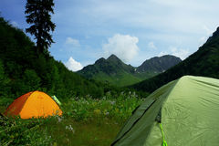 Tent in mountains with beautiful summer landscape. Tourist tent in mountains with beautiful summer landscape on a background of mountains, forests and Alpine Stock Photo