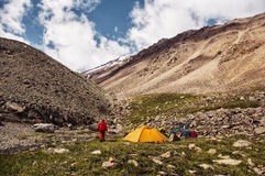 Tent in the mountains. A camp in the mountains on the grass, snow and glaciers can be seen Royalty Free Stock Images